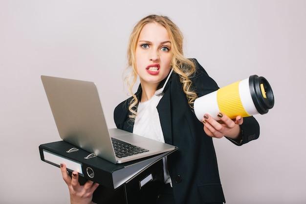 Ritratto occupato arrabbiato giovane imprenditrice in abito formale con laptop, cartella, scatola, caffè per andare nelle mani a parlare sul telefono, alla ricerca. essere in ritardo, lavoro, gestione, riunioni, lavoro