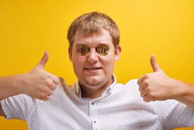 Ritratto orizzontale del ragazzo grasso allegro con bitcoin negli occhi su sfondo giallo. concetto di valuta virtuale digitale, crescita di criptovaluta sul mercato internet, ricchezza e successo