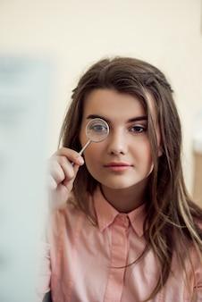 Ritratto orizzontale della bella donna focalizzata su appuntamento con oculista tenendo la lente e guardando attraverso di essa mentre si cerca di leggere il grafico a parole per controllare la visione. eyecare e concetto di salute