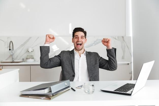 Ritratto orizzontale di felice uomo senza barba in tuta urlando e stringendo i pugni, mentre si lavora in ufficio sul computer portatile