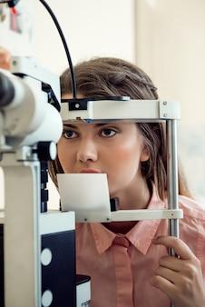 Ritratto orizzontale di mirata donna europea che prova la vista mentre guarda attraverso il microbioscopio, seduto in un ufficio specializzato, che vuole scegliere gli occhiali appropriati per vedere meglio