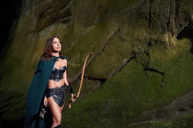 Ritratto orizzontale di un arciere medievale femminile che indossa un mantello verde che riposa all'aperto che cammina attraverso il bosco con un arco nel suo cosplay delle tribù del cacciatore delle amazzoni di caccia del copyspace della mano.