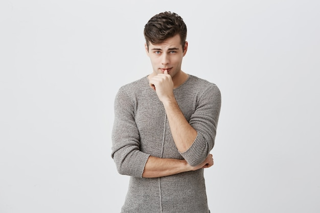 Ritratto orizzontale di uomo caucasico attraente serio sicuro che tiene la mano sotto il mento, toccando le labbra, indossando abiti casual. lo studente maschio premuroso posa allo studio