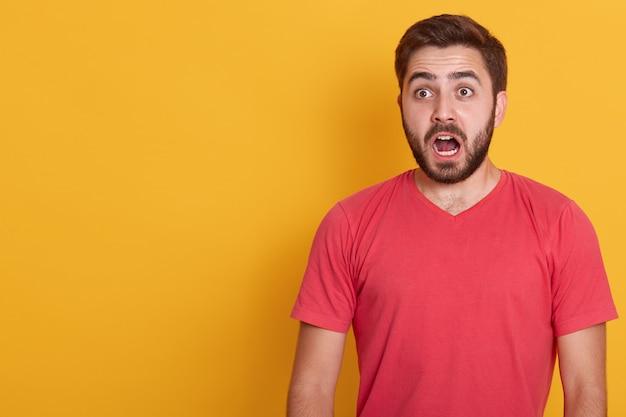 Ritratto orizzontale di uomo stupito della brunetta, che indossa una camicia casual rossa, pone contro il giallo