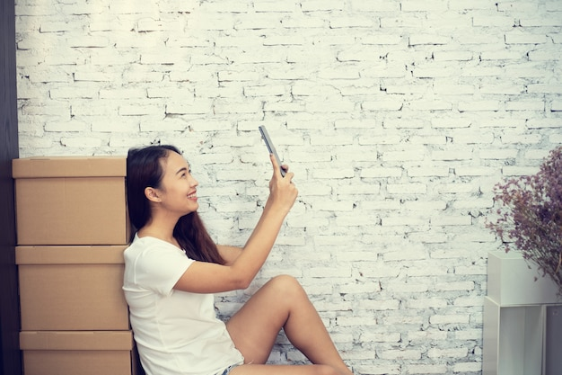 Ritratto per le giovani donne felici che si siedono sul pavimento facendo uso della compressa digitale dello smart phone