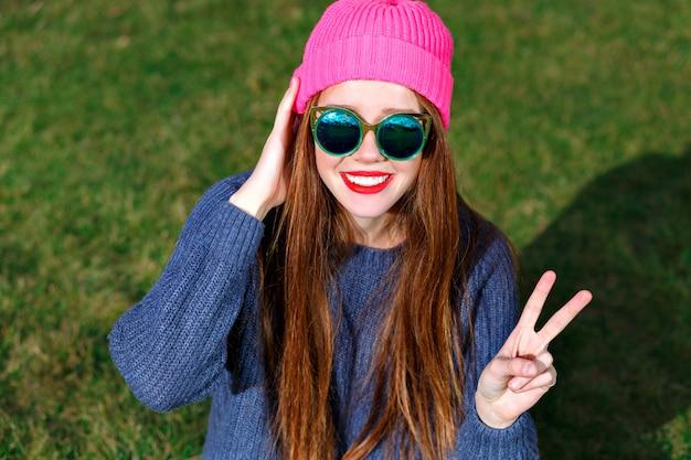 Ritratto positivo soleggiato della donna hipster sorridente felice, in posa al parco, viaggi, vacanze, gioia, mostra v dai suoi cercatori, umore primaverile, maglione e cappello.
