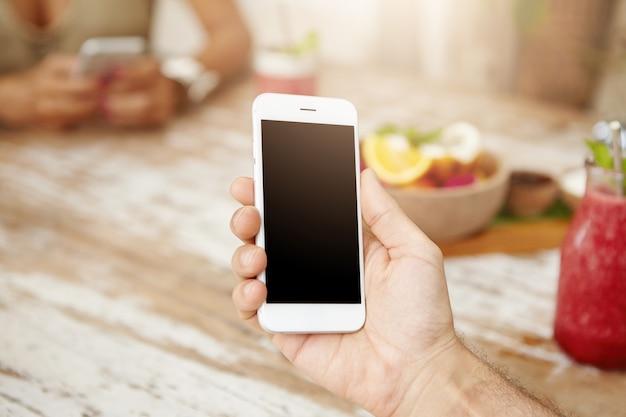 Ritratto potato di internet maschio caucasico di ricerca a scansione sul suo smart phone bianco