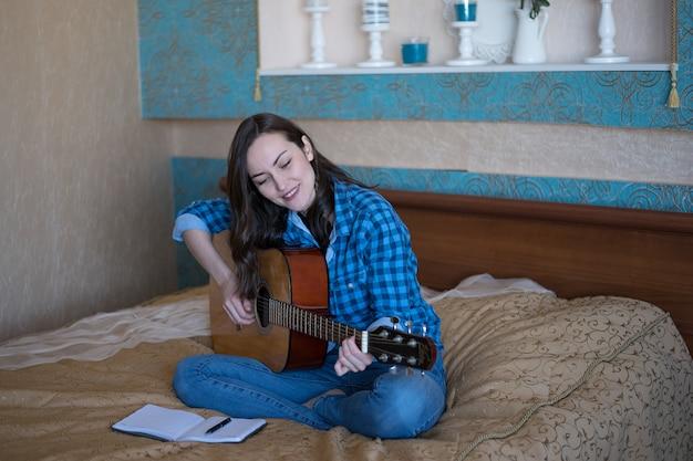 Ritratto reale di una giovane donna che impara a suonare la chitarra acustica. il concetto di creatività