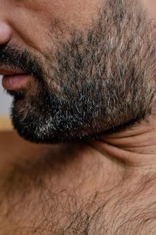 Ritratto ritagliato del primo piano di un uomo con setola dai capelli grigia o stoppia.