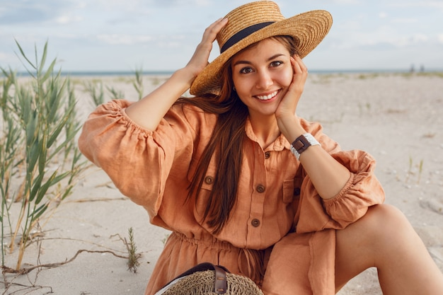Ritratto romantico della donna sorridente in cappello di paglia e vestito di lino alla moda. ragazza vaga agghiacciante vicino all'oceano. tendenza moda estiva.