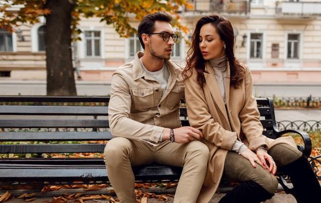Ritratto romantico di giovani belle coppie nell'amore che abbraccia e che bacia sul banco nel parco di autunno. indossa un elegante cappotto beige.