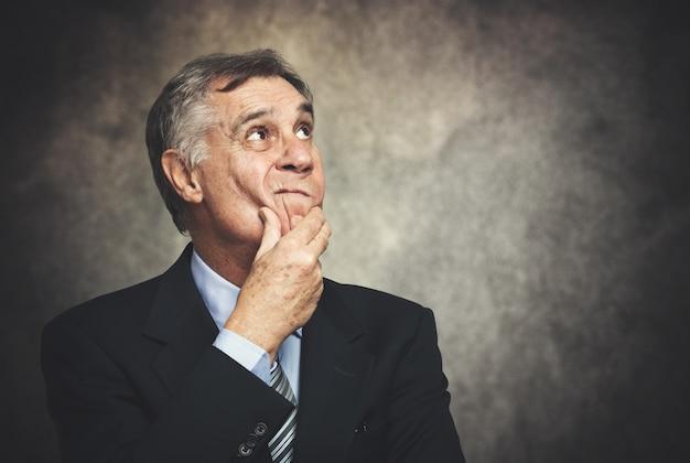 Ritratto scettico dell'uomo d'affari su una priorità bassa grungy