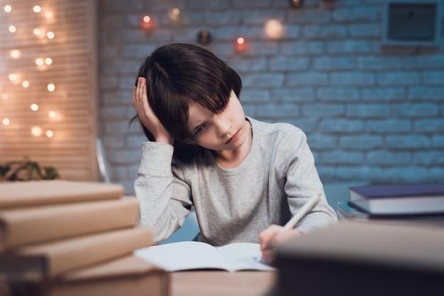 Ritratto scolaro estremamente stanco che fa i compiti