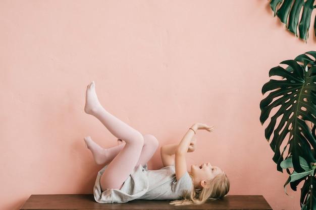 Ritratto sconosciuto di piccola ragazza bionda felice che si trova sulla tavola con la bocca e le mani aperte con i piedini in su in aria.
