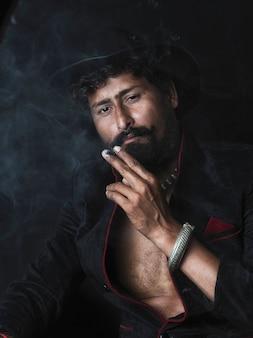 Ritratto scuro artistico del giovane bello. il giovane fuma il sigaro