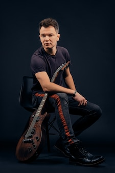 Ritratto scuro del musicista che si siede sulla sedia con la chitarra