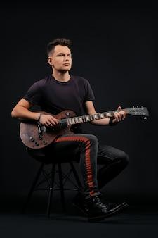 Ritratto scuro dell'uomo che canta e che gioca elettro chitarra
