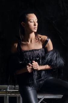 Ritratto scuro della ragazza graziosa in maglia della pelliccia e pantaloni di cuoio su fondo scuro