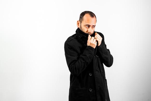 Ritratto semplice e pulito dell'uomo di mezza età che indossa il suo impermeabile nero per nascondere il viso.