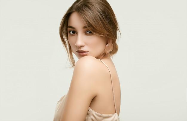 Ritratto sensuale del modello della donna di fascino isolato su bianco