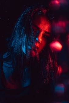 Ritratto sensuale della ragazza solitaria malinconica triste dietro vetro con le gocce di pioggia