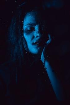 Ritratto sensuale della ragazza triste attraverso il vetro con le gocce di pioggia