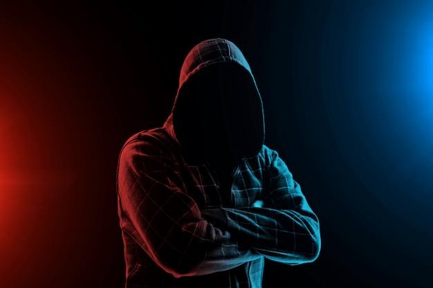 Ritratto, silhouette di un uomo in un cappuccio su uno sfondo nero, la sua faccia non è visibile.