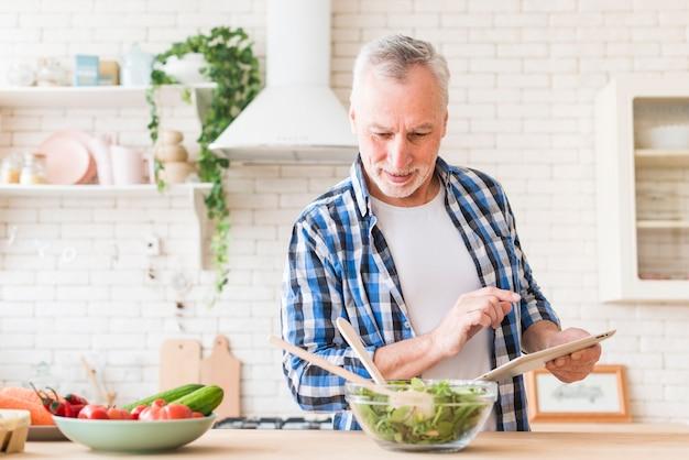 Ritratto sorridente dell'uomo senior che prepara alimento facendo uso della compressa digitale nella cucina