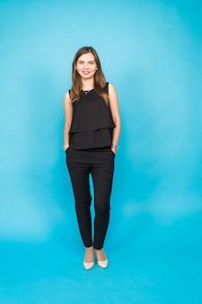 Ritratto sorridente della giovane donna sulla parete blu