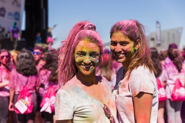 Ritratto sorridente delle giovani donne con la polvere di holi sul loro fronte che esamina macchina fotografica