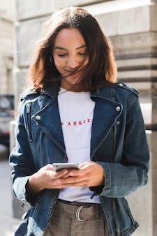 Ritratto sorridente di giovane donna alla moda che per mezzo del telefono cellulare