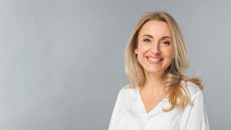 Ritratto sorridente di giovane donna di affari bionda che sta contro il fondo grigio