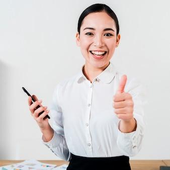 Ritratto sorridente di giovane donna di affari che giudica cellulare disponibile che mostra pollice sul segno