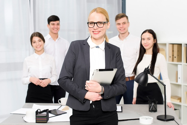 Ritratto sorridente di giovane donna di affari che tiene compressa digitale a disposizione che sta davanti al suo collega