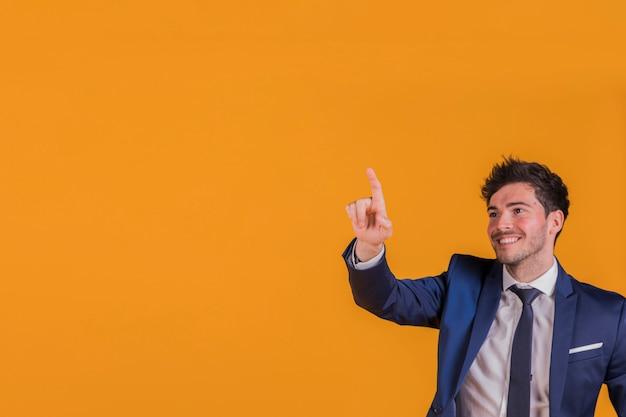 Ritratto sorridente di giovane uomo d'affari che indica la sua barretta a qualcosa su una priorità bassa arancione