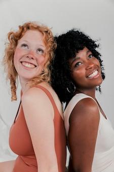 Ritratto sorridente di giovani donne africane e caucasiche che si siedono di nuovo alla parte posteriore che osserva in su