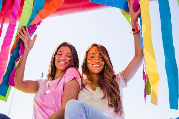 Ritratto sorridente di giovani donne con colore di holi sul loro fronte che guarda l'obbiettivo