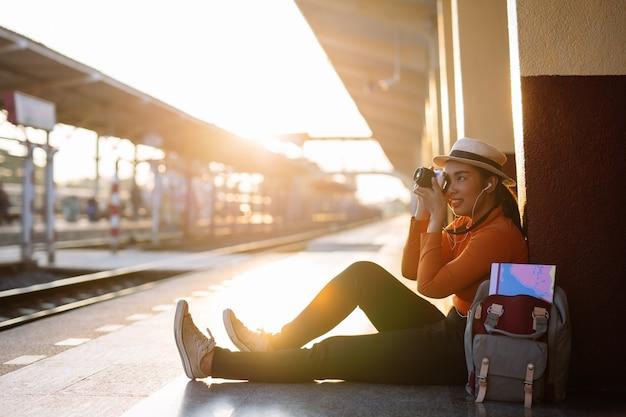 Ritratto sorridente di stile di vita di estate all'aperto della giovane donna graziosa divertendosi alla stazione ferroviaria.