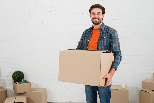 Ritratto sorridente di un giovane che porta la scatola di cartone che si leva in piedi contro la parete bianca