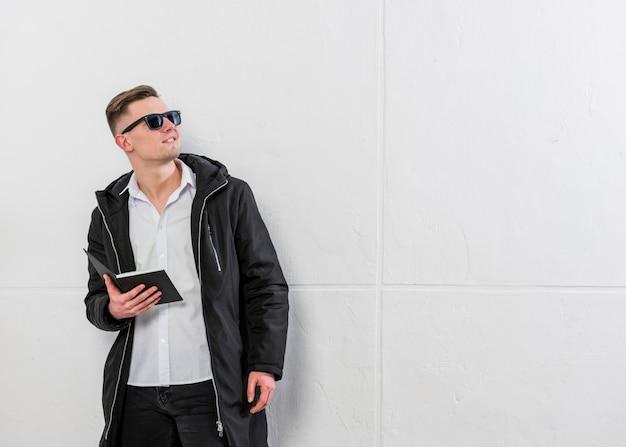 Ritratto sorridente di un giovane uomo che tiene in mano il libro in cerca di distanza