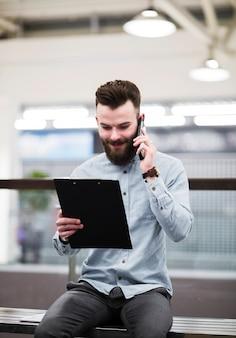 Ritratto sorridente di un giovane uomo d'affari che esamina appunti che parla sul telefono cellulare