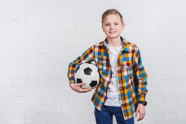 Ritratto sorridente di un pallone da calcio della tenuta del ragazzo che sta in piedi contro il muro di mattoni bianco