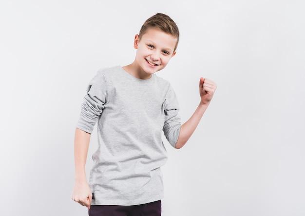 Ritratto sorridente di un ragazzo che serra il suo pugno che si leva in piedi contro la priorità bassa bianca