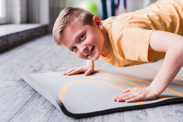 Ritratto sorridente di un ragazzo che si esercita esaminando macchina fotografica