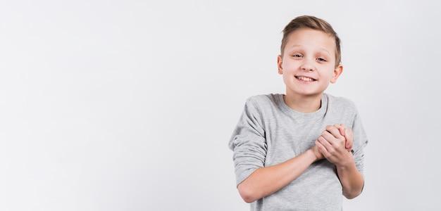 Ritratto sorridente di un ragazzo che unisce le mani che guardano alla macchina fotografica contro fondo bianco