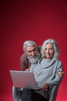 Ritratto sorridente di un uomo anziano che abbraccia la sua moglie da dietro seduto sulla sedia con il portatile