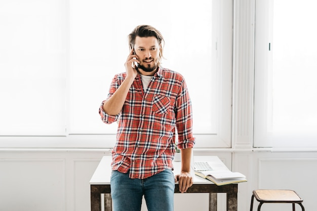 Ritratto sorridente di un uomo che si siede sul bordo del tavolo a parlare sul telefono cellulare