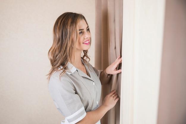 Ritratto sorridente di una cameriera femminile che guarda fuori attraverso la finestra