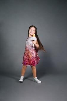 Ritratto sorridente di una canzone di canto del microfono della tenuta della ragazza contro fondo grigio