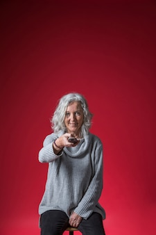 Ritratto sorridente di una donna senior che si siede sulle feci che cambiano il canale con telecomando contro il contesto rosso